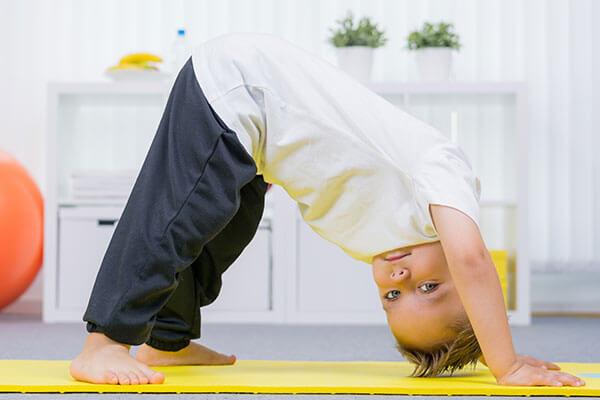 Advizi - Enfant sur un tapis de gym jaune réalisant une pirouette