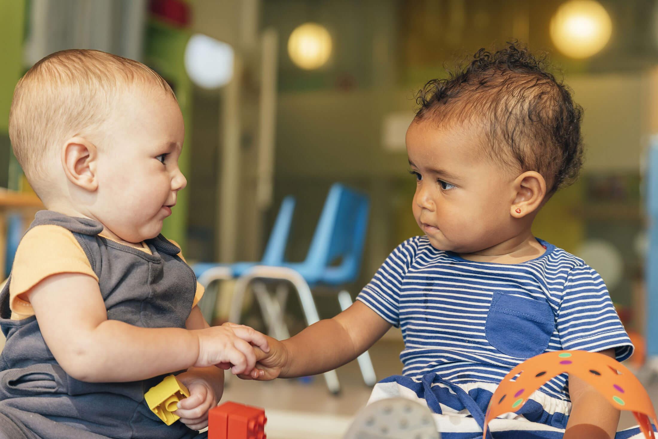 Advizi - La photo représente deux bébés qui se serrent la main. Un des bébés est de type européen et l'autre de type africain. Ils se regardent dans les yeux.