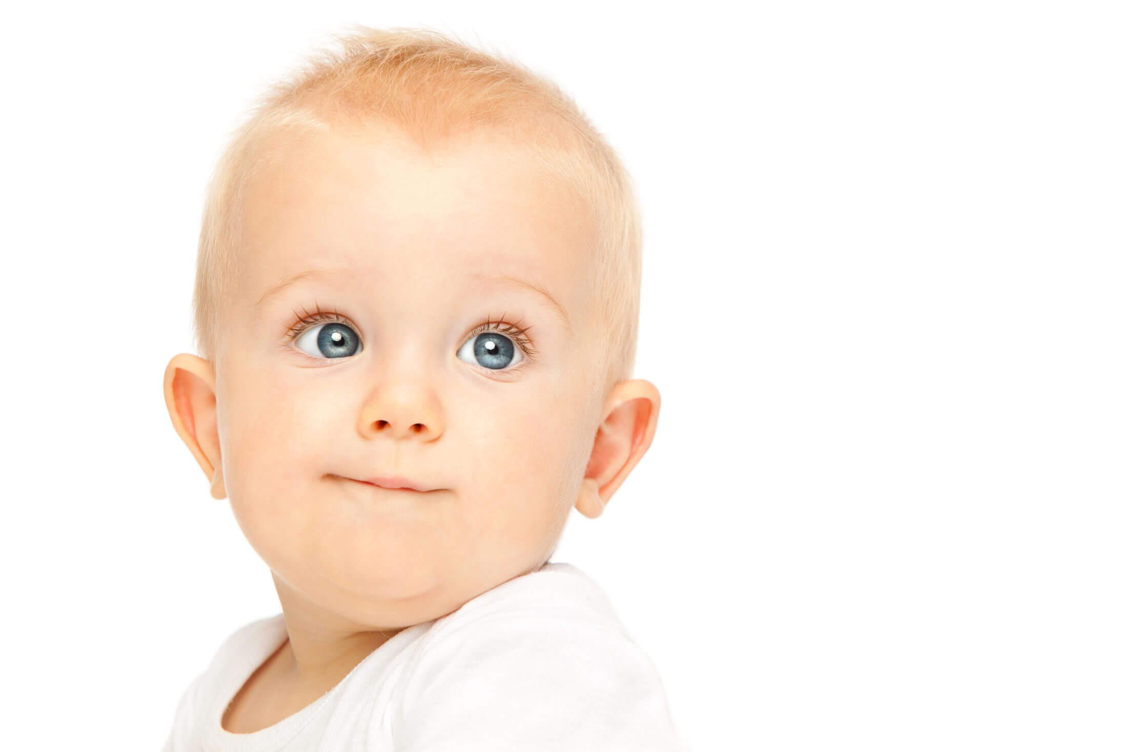 Advizi - La photo représente un bébé blond aux yeux bleus. Elle est sur fond blanc