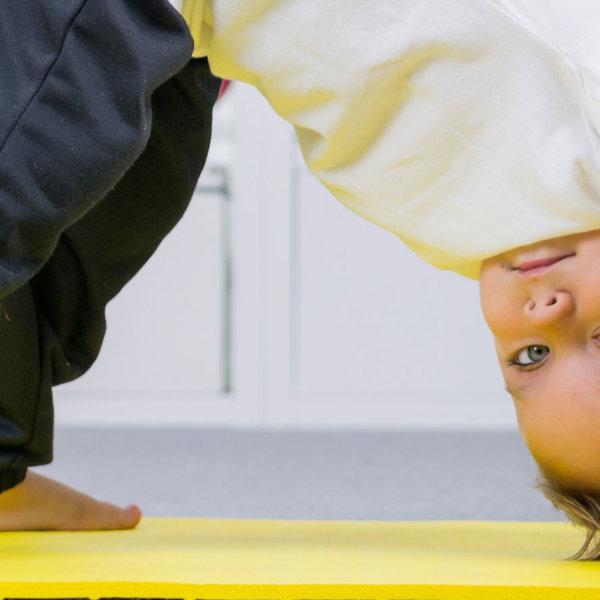 Advizi - Enfant sur un tapis de gym jaune réalisant une pirouette; La photo est prise en gros plan.