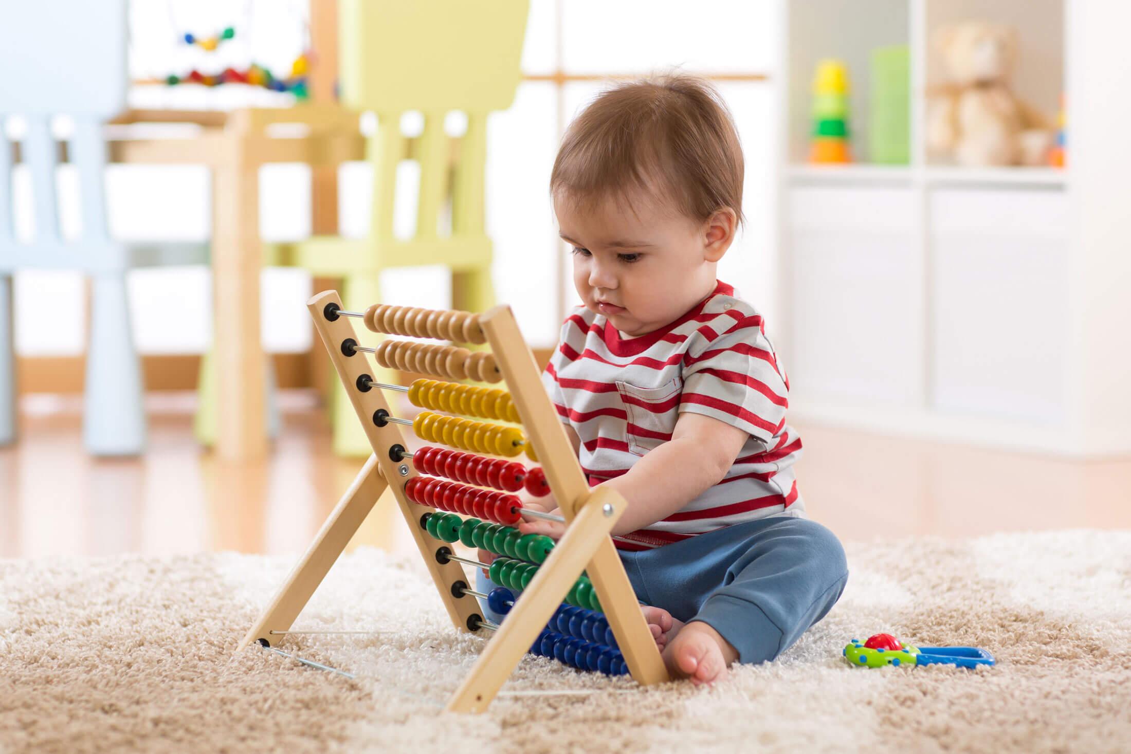 Advizi - La photo représente un bébé assis devant un boulier en bois.
