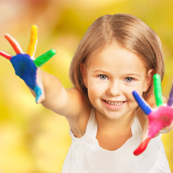 Advizi - La photo représente une petite fille d'environ 4 ans les mains en l'air qui sourit. Ses mains sont peinturées multicolores.