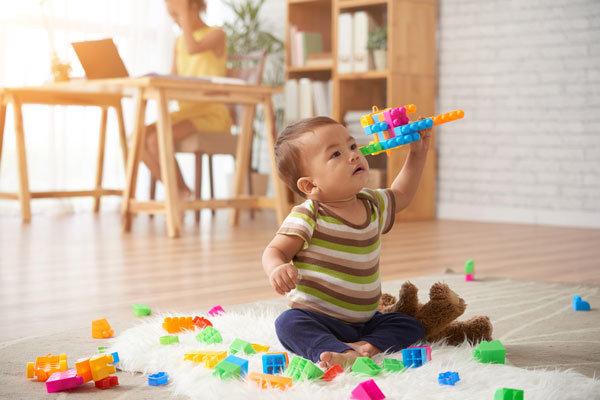 Advizi - La photo représente un bébé assis qui fait voler un avion en lego multicolore.