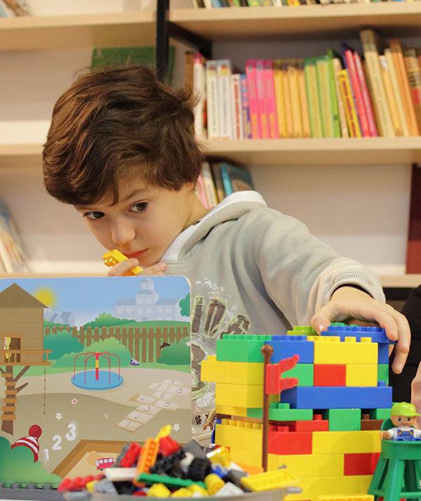 Advizi - La photo représente un petit garçon d'environ 3 ans réalisant une construction en lego. Une bibliothèque est présente en 2nd plan.